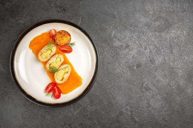 Вид сверху вкусные картофельные пироги с тыквой внутри тарелки на сером фоне печь цветное блюдо ломтик ужина