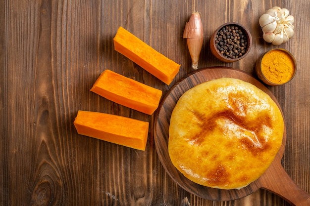 조미료와 나무 책상에 얇게 썬 호박이있는 맛있는 호박 파이 케이크 파이 빵 오븐 핫케이크