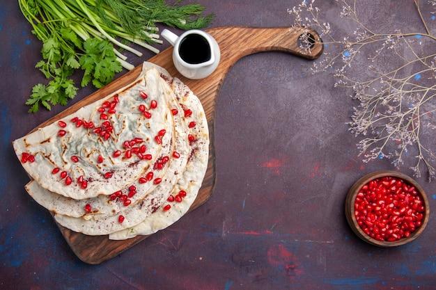 ひき肉と新鮮なザクロを暗い表面に載せたおいしいクタブピタの上面図生地ピタ肉ミール