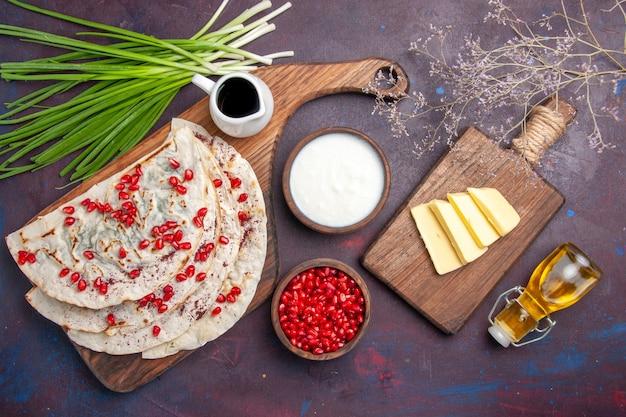 Вид сверху вкусные кутабс-питы с мясным оливковым маслом и свежими гранатами на темной поверхности тесто лаваш мясная мука выпечка