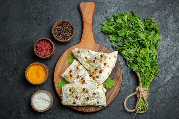 Vista dall'alto deliziosi qutab con diversi condimenti e verdure su uno spazio grigio