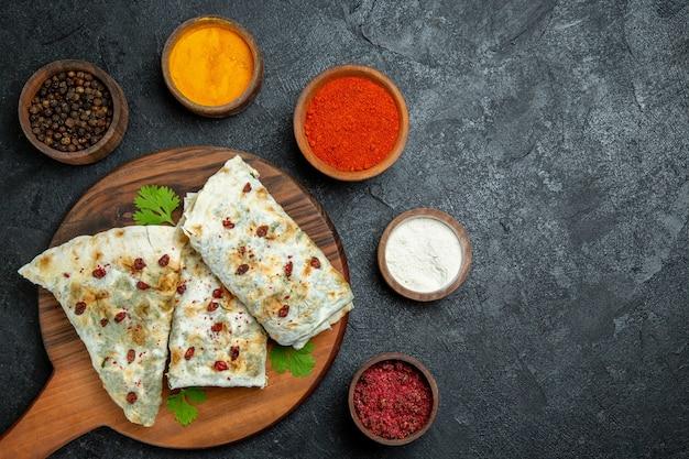 灰色の床の食事調理生地肉油食品にさまざまな調味料を使ったおいしいクタブの上面図