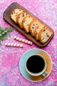 Vista dall'alto deliziosa torta all'uvetta affettata con una tazza di caffè sulla superficie rosa cuocere in forno il colore del biscotto del biscotto dolce dello zucchero