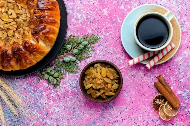 上面図ピンクの背景にコーヒーカップとおいしいレーズンケーキパイシュガー甘いビスケットクッキーの色を焼く