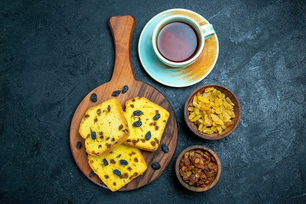 Vista dall'alto deliziose torte di uvetta con uvetta fresca e tazza di tè su uno spazio buio