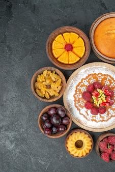 トップビューグレーの背景にフルーツとレーズンのおいしいラズベリーケーキ甘いパイフルーツベリーケーキクッキー