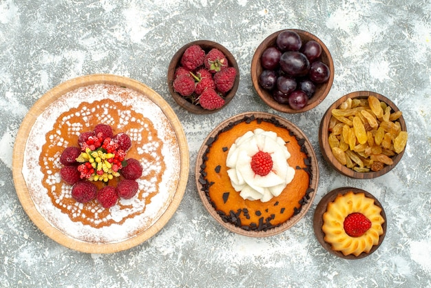 Top view delicious raspberry cake with fruits raisins and pie on white background cake fruit pie cookie tea berries