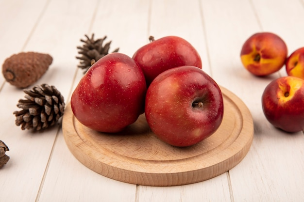 Vista dall'alto di deliziose mele rosse su una tavola da cucina in legno con pesche e pigne isolate su una superficie di legno bianca