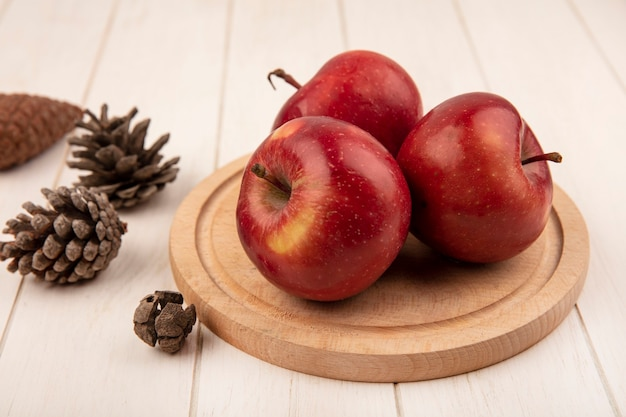 Top view of delicious red apples on a wooden kitchen board with pine cones isolated on a white wooden surface
