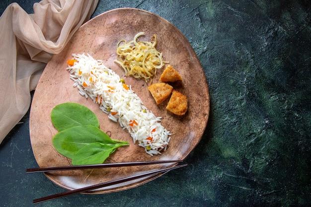 어두운 책상에 접시 안에 녹색 잎 콩과 고기 상위 뷰 맛있는 쌀