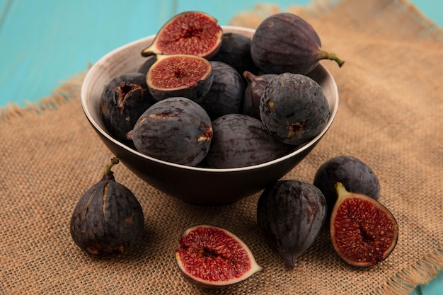 Top view of delicious ripe black mission figs on a bowl on a sack cloth on a blue wall