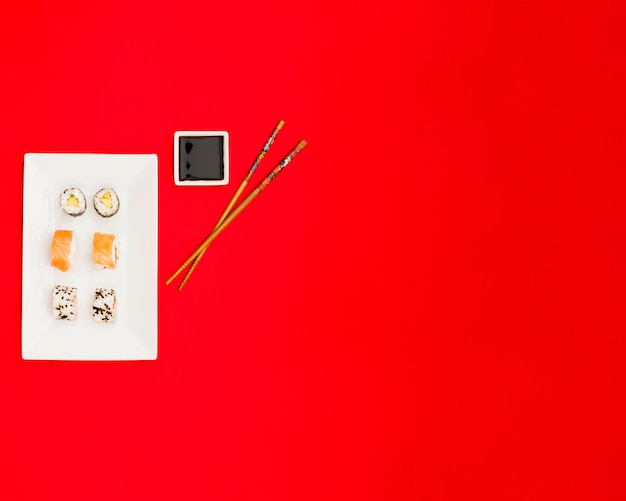 Top view of delicious rolls with soya sauce and chopsticks over bright red background