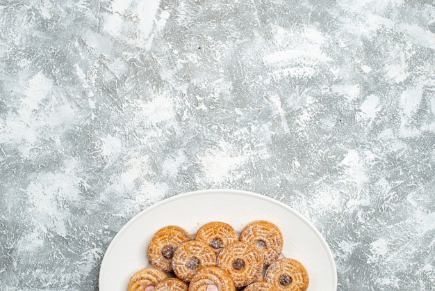 Vista dall'alto deliziosi biscotti rotondi all'interno del piatto su uno spazio bianco
