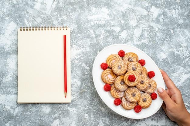 Vista dall'alto deliziosi biscotti rotondi con confettura di lamponi su uno spazio bianco chiaro
