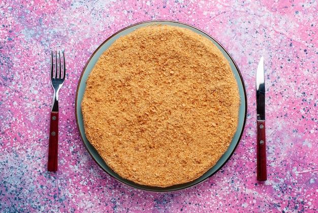 Вид сверху вкусный круглый торт внутри стеклянной тарелки на ярко-розовом столе, пирог, бисквит, сладкая выпечка, сахар