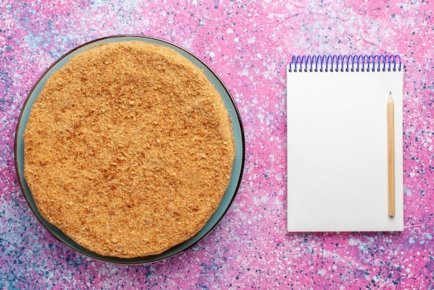 Вид сверху вкусный круглый торт внутри стеклянной тарелки с блокнотом на ярком столе торт пирог бисквит сладкий выпечка сахар