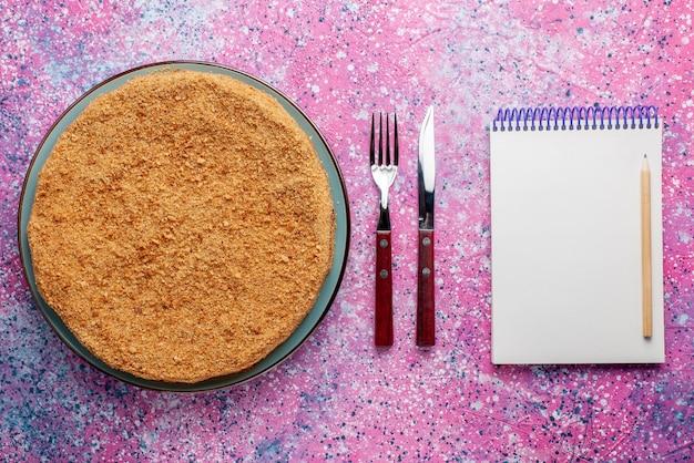 Вид сверху вкусный круглый торт внутри тарелки со столовыми приборами и блокнотом на ярком столе торт пирог бисквит сладкая выпечка сахар