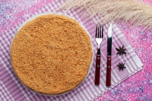 Вид сверху вкусный круглый торт внутри тарелки со столовыми приборами на ярко-розовом столе, пирог, бисквит, сладкая выпечка