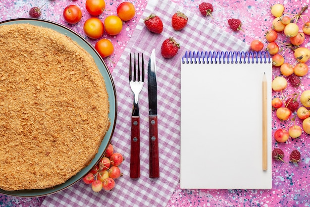 明るいピンクのデスクケーキパイビスケット甘い焼き砂糖の上の果物とメモ帳とプレートの中のおいしい丸いケーキの上面図