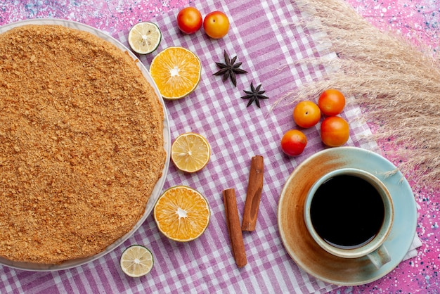 明るいピンクのデスクケーキパイビスケットスウィートベイクにフルーツと紅茶を添えたプレート内のおいしい丸いケーキの上面図