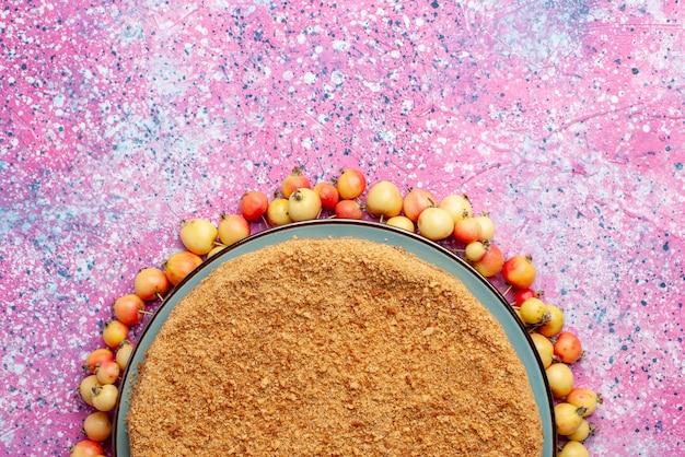 明るいピンクのデスクケーキビスケットの甘い焼き砂糖に甘いチェリーが並んだプレートの内側のおいしい丸いケーキの上面図