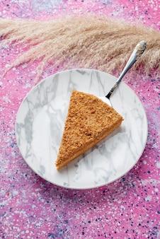 明るいピンクのデスクケーキパイビスケットスイートベイクのプレート内のおいしい丸いケーキスライスの上面図