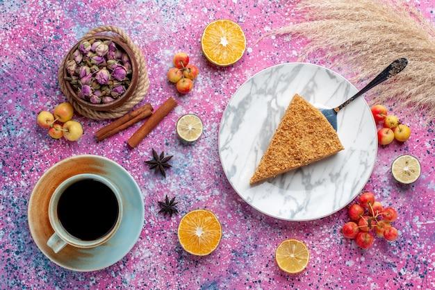 明るいピンクのデスクケーキパイビスケットスウィートベイクにお茶を入れたプレートの内側のおいしい丸いケーキスライスの上面図