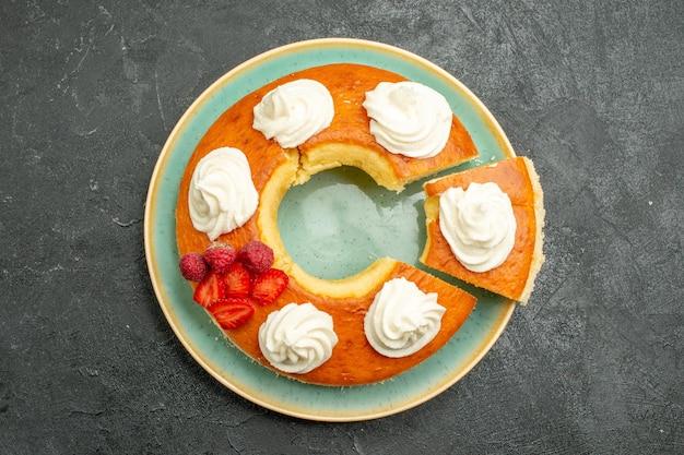 Vista dall'alto deliziosa torta rotonda affettata con crema bianca sullo sfondo grigio biscotto torta biscotto torta tè dolce