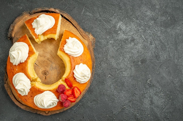 Vista dall'alto deliziosa torta rotonda affettata con crema bianca su sfondo grigio biscotti torta biscotto torta tè dolce