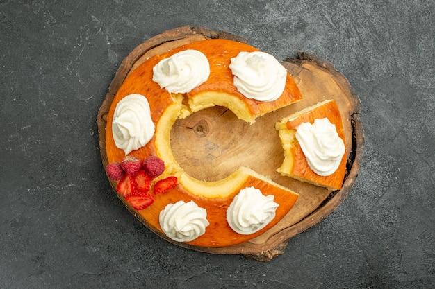 Вид сверху вкусный круглый пирог нарезанный белым кремом на сером фоне печенье бисквитный пирог сладкий чай