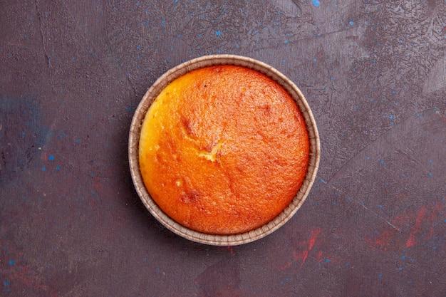 Вид сверху вкусный круглый пирог, сладкая выпечка на темном фоне, бисквитное тесто, пирог, сахар, сладкий чай