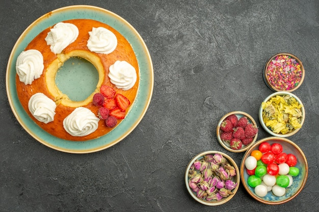 Top view delicious round pie with candies on grey desk sugar cookie biscuit cake pie sweet tea