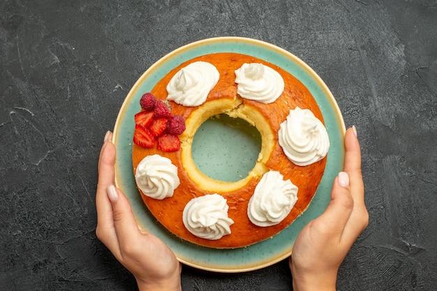 Вид сверху вкусный круглый пирог с фруктами и сливками на темном фоне сахарное печенье бисквитный пирог сладкий чай