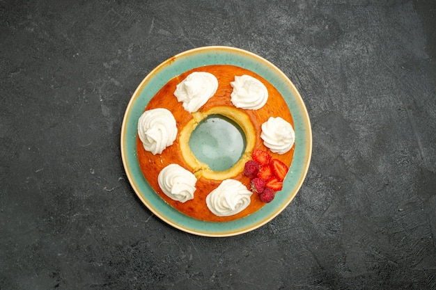 Top view delicious round pie with fruits and cream on dark background tea sugar cookie biscuit cake pie sweet