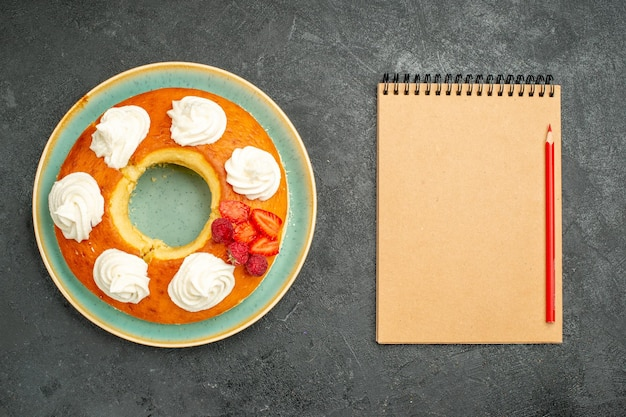 Vista dall'alto deliziosa torta rotonda con frutta e crema su sfondo scuro tè zucchero biscotto torta biscotto dolce