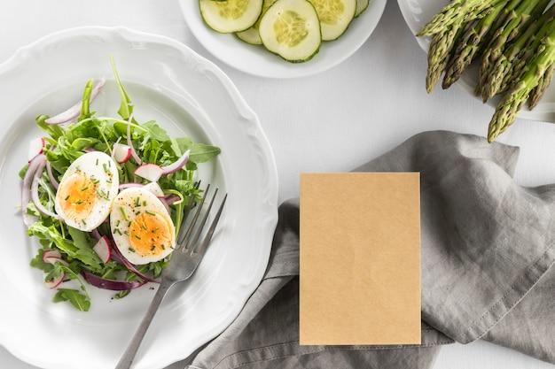 Вид сверху вкусный салат на белой тарелке с пустой картой