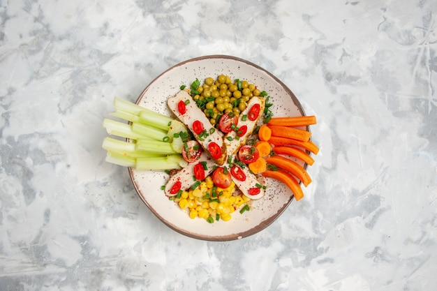 Vista dall'alto di una deliziosa insalata su un piatto sulla superficie bianca macchiata