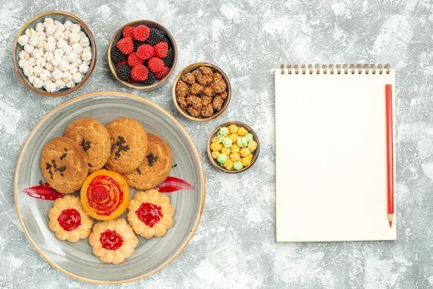 上面図白い背景の上のクッキーとキャンディーとおいしい砂のビスケットビスケット甘いクッキーシュガーケーキティー