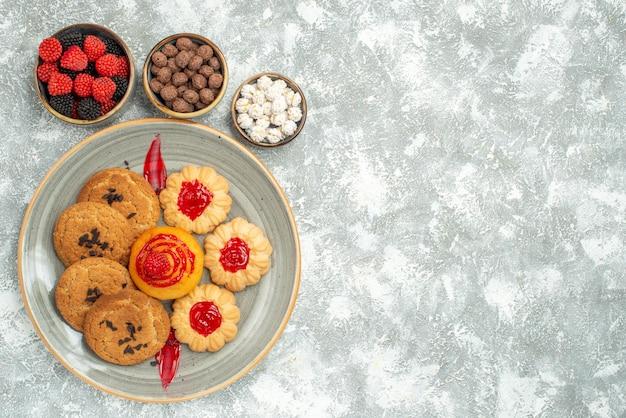 上面図白い背景の上のクッキーとキャンディーとおいしい砂のビスケット砂糖ビスケットケーキクッキーティースイート