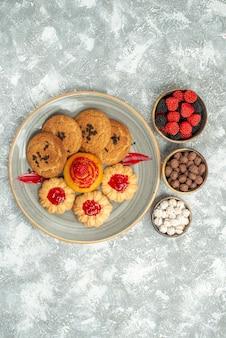 Вид сверху вкусного песочного печенья с печеньем и конфетами на белом фоне сахарный бисквитный торт печенье чай сладкий пирог