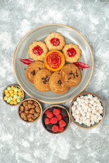 Top view delicious sand biscuits with cookies and candies on light white background biscuit sweet sugar cake tea cookie