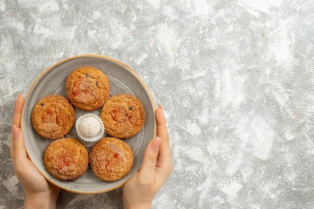 Vista dall'alto deliziosi biscotti di sabbia all'interno del piatto su sfondo bianco chiaro