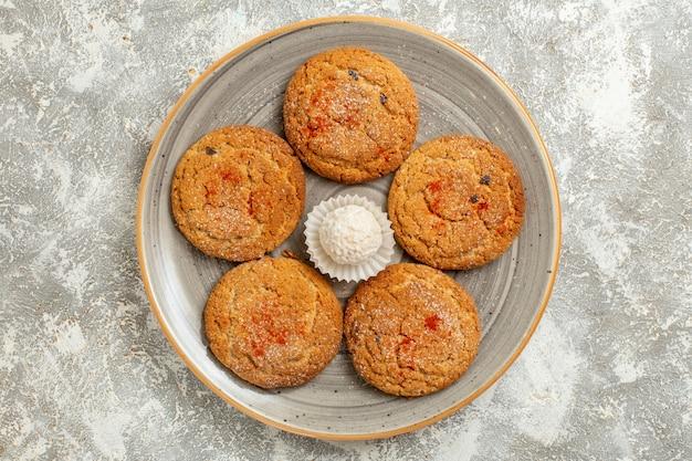 Вид сверху вкусного песочного печенья внутри тарелки на белом фоне
