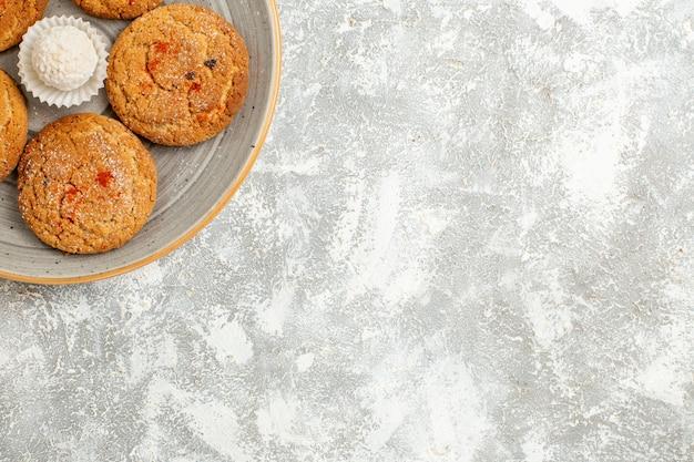 Vista dall'alto deliziosi biscotti di sabbia all'interno del piatto sulla scrivania bianca