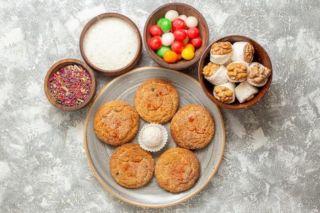 上面図白い背景の上のキャンディーとおいしい砂のクッキー