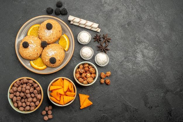 暗い表面の甘いフルーツコッキービスケットにチップとオレンジスライスが入ったトップビューのおいしいサンドクッキー