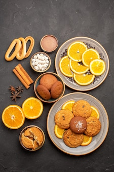 Вид сверху вкусное песочное печенье со свежими апельсинами на темном фоне, печенье, сахар, фрукты, бисквит, сладкие цитрусовые