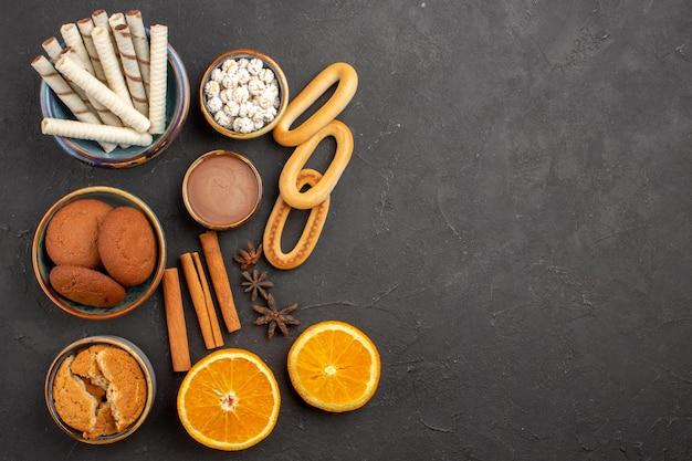 Вид сверху вкусное песочное печенье со свежими апельсинами на темном фоне, печенье, сахар, фрукты, сладкое цитрусовое печенье