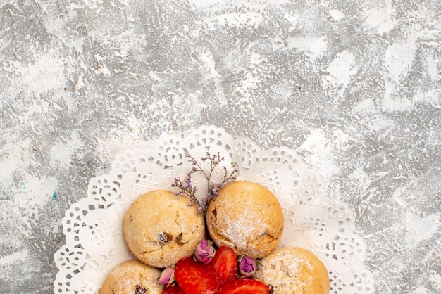 Top view of delicious sand cookies with fresh strawberries on a white surface