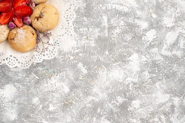 Vista dall'alto di deliziosi biscotti di sabbia con fragole fresche sulla superficie bianca